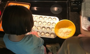 My daughter and I making these cheesy potato bites. Pictured is a bowl with the mix, plus a mini-muffin tin filled.