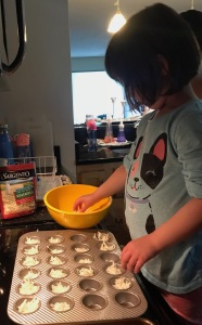 My daughter putting the mix from the bowl into the mini muffin tin